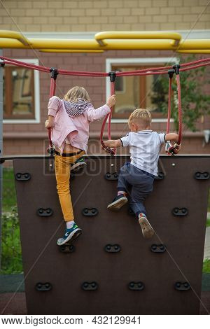 Caucasian Boy And A Girl Climb The Climbing Wall In The Playground.