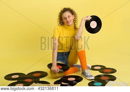 Girl Sitting On Floor Surrounded By Vinyl Records. Portrait Of Happy Curly Girl Wearing Bright Yello