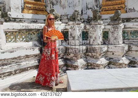 Travel To Asia. Portrait Of Young Caucasian Blonde Girl Traveler With Traditional Asian Fan In Hands