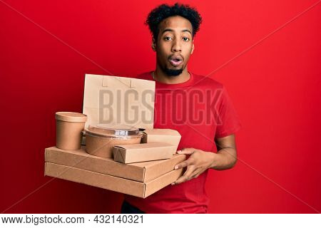 Young african american man with beard holding take away food afraid and shocked with surprise and amazed expression, fear and excited face.