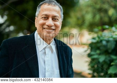 Middle age southeast asian man standing and smiling confident by the park