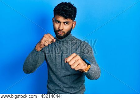 Arab man with beard wearing turtleneck sweater punching fist to fight, aggressive and angry attack, threat and violence