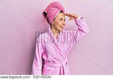 Young blonde woman wearing shower towel cap and bathrobe very happy and smiling looking far away with hand over head. searching concept.