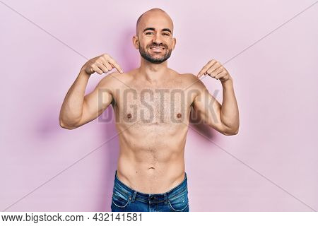 Young bald man standing shirtless looking confident with smile on face, pointing oneself with fingers proud and happy.