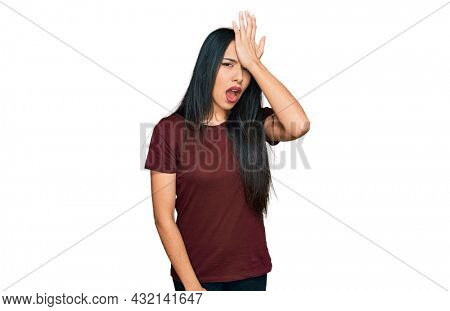 Young hispanic girl wearing casual t shirt surprised with hand on head for mistake, remember error. forgot, bad memory concept.