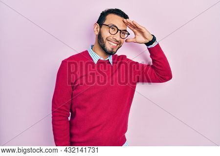 Hispanic man with beard wearing business shirt and glasses very happy and smiling looking far away with hand over head. searching concept.