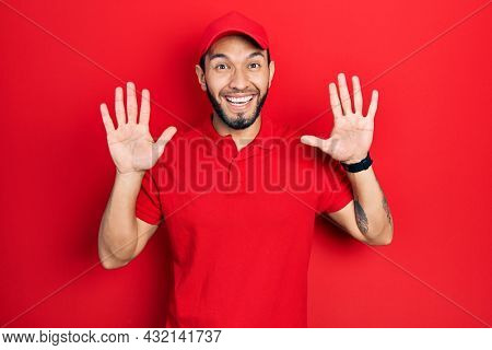 Hispanic man with beard wearing delivery uniform and cap showing and pointing up with fingers number ten while smiling confident and happy.