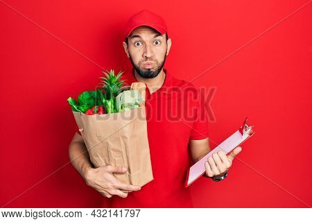 Hispanic man with beard wearing courier uniform with groceries from supermarket and clipboard puffing cheeks with funny face. mouth inflated with air, catching air.