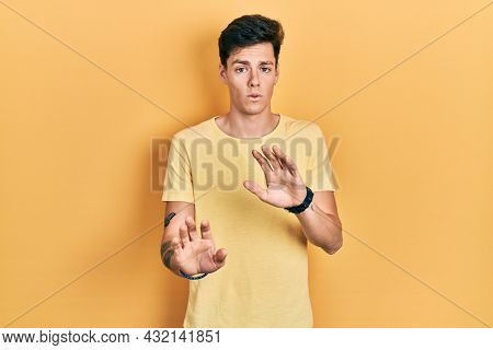 Young hispanic man wearing casual yellow t shirt moving away hands palms showing refusal and denial with afraid and disgusting expression. stop and forbidden.