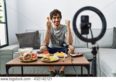 Young hispanic man recording eating food video with smartphone at home screaming proud, celebrating victory and success very excited with raised arm
