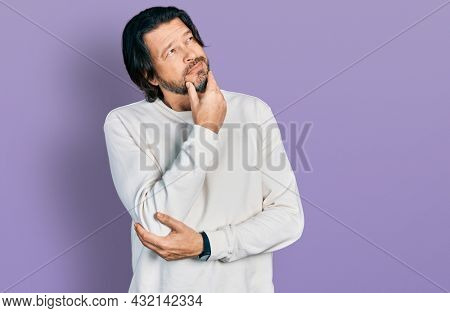 Middle age caucasian man wearing casual clothes with hand on chin thinking about question, pensive expression. smiling with thoughtful face. doubt concept.
