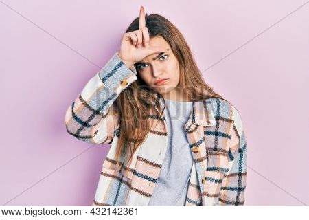 Young caucasian girl wearing casual clothes making fun of people with fingers on forehead doing loser gesture mocking and insulting.
