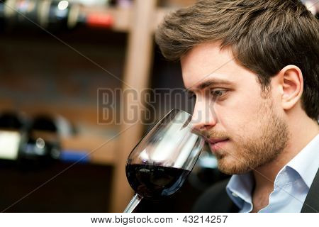 Man tasting a glass of red wine
