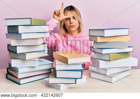 Young caucasian woman sitting on the table with books making fun of people with fingers on forehead doing loser gesture mocking and insulting.