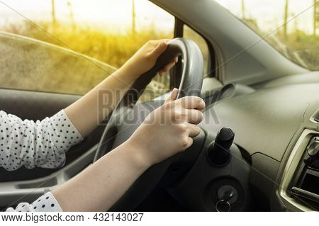 Close-up To The Hands Of A White Woman On The Steering Wheel Of A Modern Car With Black Upholstery I