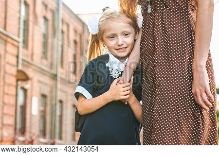 The Mother Leads The Little Girl Student To The First Grade Hand In Hand. Back To School. The Beginn