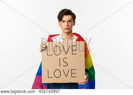 Waist-up Shot Of Young Lgbtq Male Activist, Wearing Rainbow Flag And Holding Love Is Love Card Sign