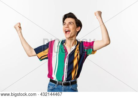 Happy Gay Man Celebrating Victory, Raising Hands Up And Rejoicing Of Winning, Tirumphing While Stand