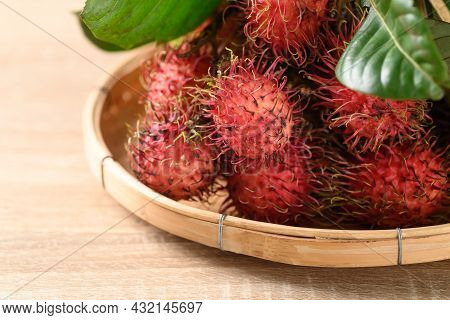 Ripe Rambutan Fruit In A Bamboo Basket On Wooden Background, Rambutan Is Tropical Fruit And Native S