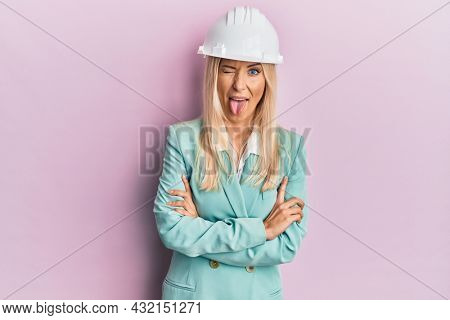 Young blonde woman wearing architect hardhat sticking tongue out happy with funny expression.