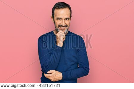 Middle age hispanic man wearing casual clothes looking confident at the camera with smile with crossed arms and hand raised on chin. thinking positive.
