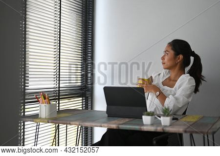 A Businesswoman Relaxing At Comfortable Office Chair And Looking Through A Window At Her Working Pla