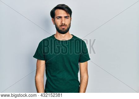 Young hispanic man wearing casual white tshirt depressed and worry for distress, crying angry and afraid. sad expression.