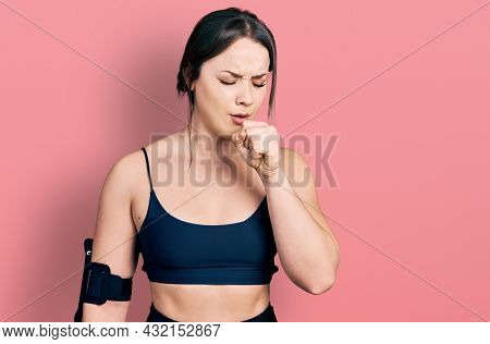 Young hispanic woman wearing sportswear feeling unwell and coughing as symptom for cold or bronchitis. health care concept.