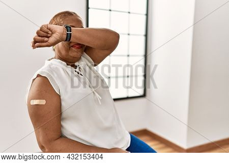 Mature hispanic woman getting vaccine showing arm with band aid smiling cheerful playing peek a boo with hands showing face. surprised and exited