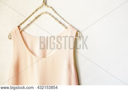 Light Pink Tank Top Hanging On A Hanger In A White Wall. Close Up And Copy Space.