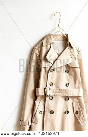 Beige Trench Coat Isolated Hanging On A Hanger In A White Wall. Close Up And Copy Space.