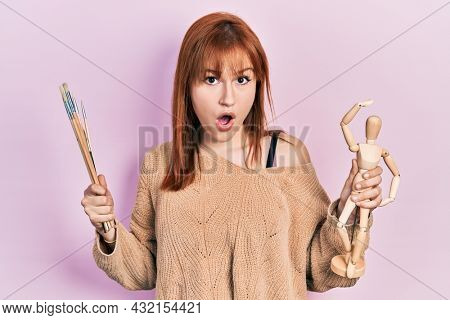 Redhead young woman holding small wooden manikin and painter brushes afraid and shocked with surprise and amazed expression, fear and excited face.