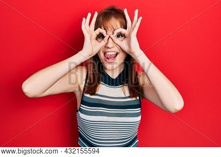Redhead young woman wearing casual t shirt doing ok gesture like binoculars sticking tongue out, eyes looking through fingers. crazy expression.