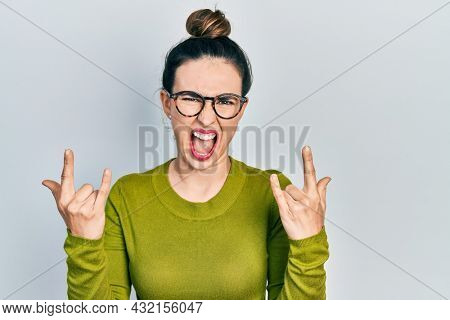Young hispanic girl wearing casual clothes and glasses shouting with crazy expression doing rock symbol with hands up. music star. heavy concept.