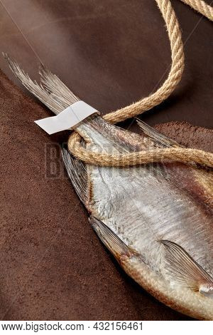 Air-dried Roach Tail With Paper Label And Coarse Rope On Brown Leather Background