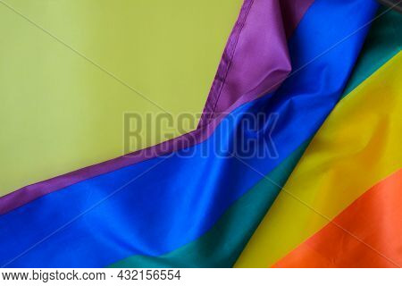 Rainbow Flag On Yellow Background With Copy Space. Rainbow Lgbtq Flag Made From Silk Material. Symbo