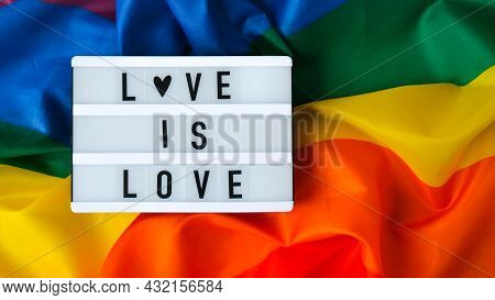 Rainbow Flag With Lightbox And Text Love Is Love. Rainbow Lgbtq Flag Made From Silk Material. Symbol