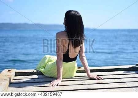 45 Years Old Russian Woman Sitting On A Pier And Looking Away Against Japanese Sea