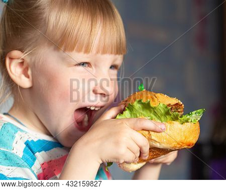 Girl 4 X Years Old Eating A Big Fast Food Hamburger. Concept Of Childrens Addiction To Fast Food, Ha