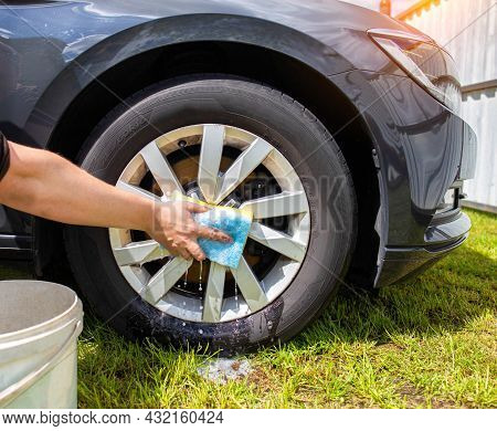 A Man Washes Rims In A Car With A Sponge And Foam And A Bucket Of Water. Hand Wash Near The House. C