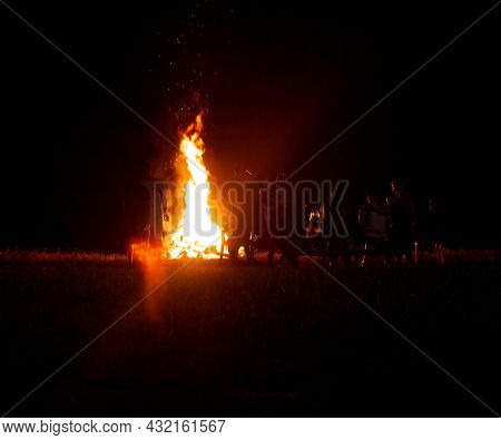 People Relax On A Holiday In The Forest Near A Large Bonfire At Night. National Holiday Background,