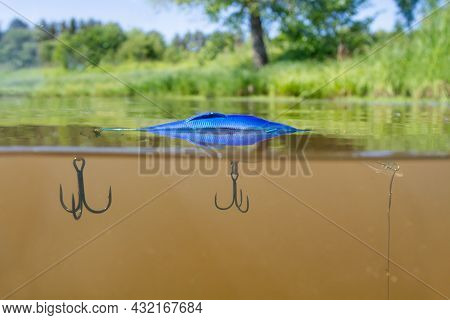 Spinning Fishing. On The Surface Of The Murky Lake Water, A Blue Wobbler Floats Attached To A Fishin