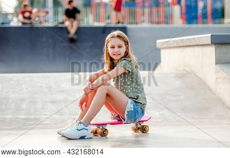 Preteen girl sitting on skateboard outdoors and looking at camera Female skater child close to city riding ramp at summer