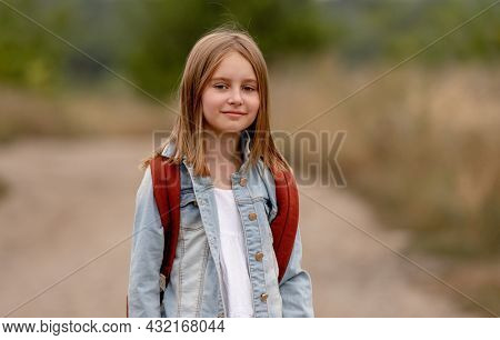 School girl with backpack in the field. Portrait of preteen child kid at nature