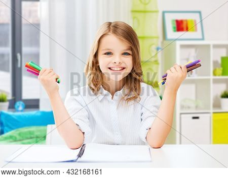 education, art and school concept - happy smiling student girl with colorful felt-tip pens over home room background