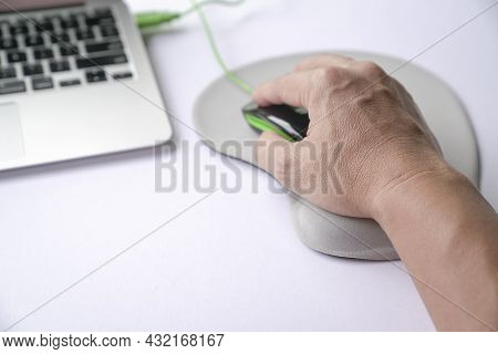 Man's Hand Clicking On Mouse, Resting His Wrist On Wrist Rest Or Support Memory Foam. Close Up Shot.