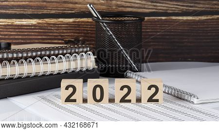 2022 Text On The Wooden Block With Notebooks On Chart