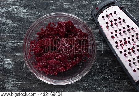 Top View Of Grated Cooked Beet In Glass Bowl And Grater On Black Background
