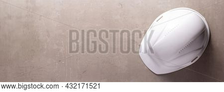 Construction helmet at gray table background texture. Hardhat on concrete floor