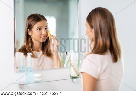 beauty, hygiene and people concept - teenage girl with cleansing sponge cleaning facial skin and looking in mirror at bathroom